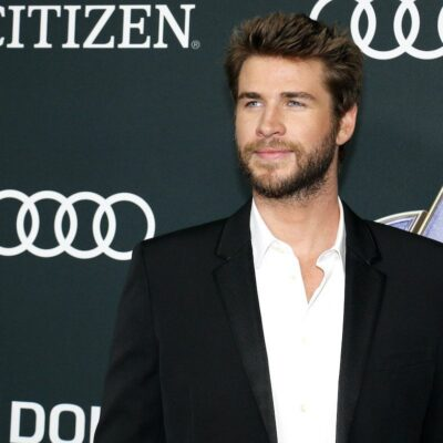 Liam Hemsworth wearing a black suit jacket and white button up smiling at a Hollywood event.