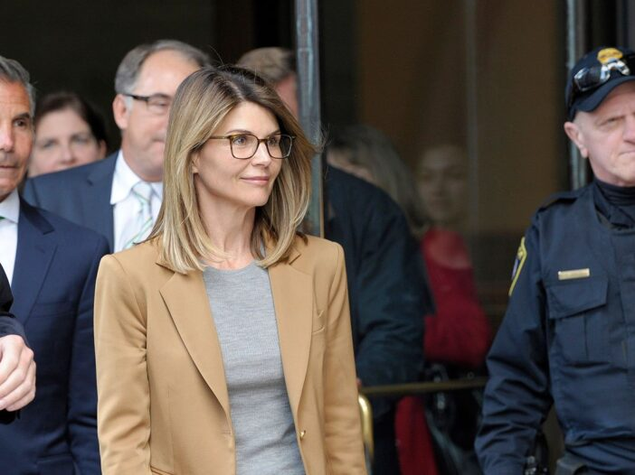 Lori Loughlin in a tan jacket walking out of the courthouse