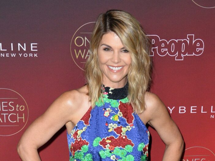 Lori Loughlin smiling in a multicolored dress against a red background