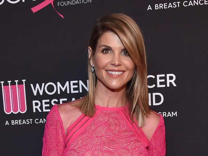 Lori Loughlin smiling in a pink dress at a charity event pre-prison