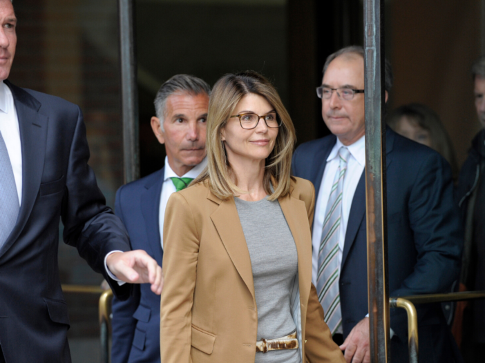 Lori Loughlin wearing tan jacket and gray top exiting a courthouse
