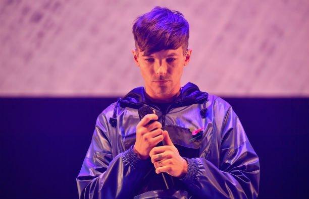 Louis Tomlinson wearing a black jacket on stage