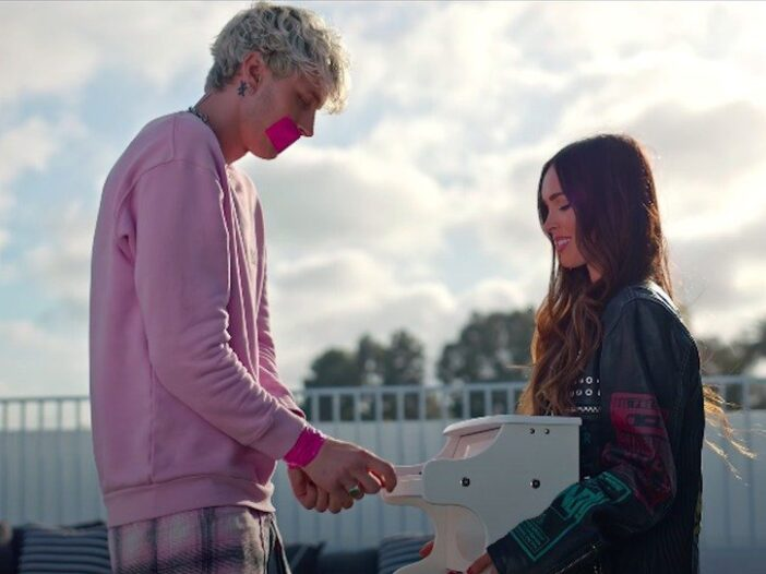 Machine Gun Kelly's Bloody Valentine video still of Kelly in a pink sweater and Megan Fox in leather