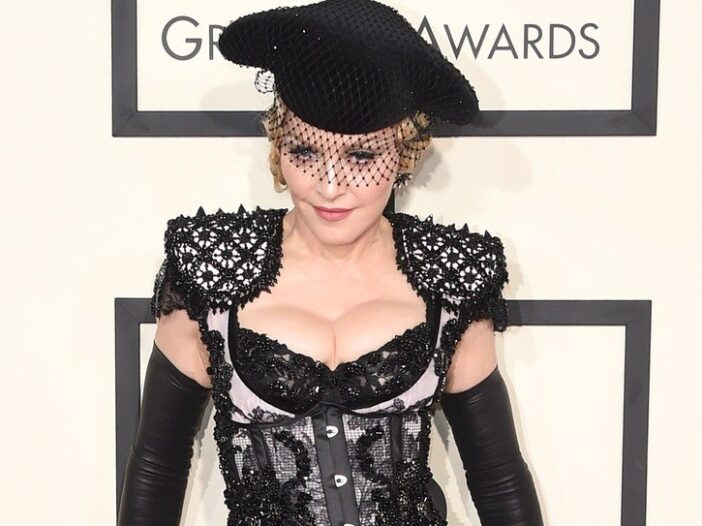 Madonna in a lacey black dress, almost like lingerie, and a black veil.