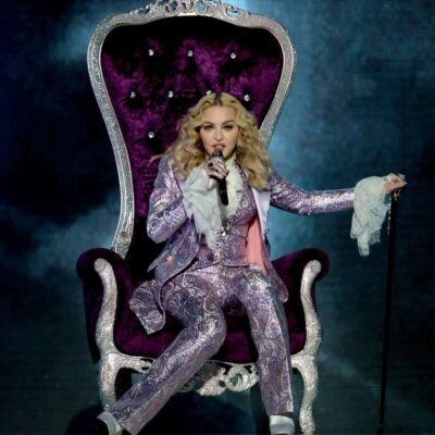 Madonna wearing a lilac suit seated on a purple throne onstage at the 2016 Billboard Music Awards du