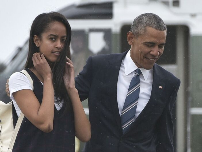 Malia Obama in a black and white dress walking with her father, Barack, who's wearing a dark suit, o
