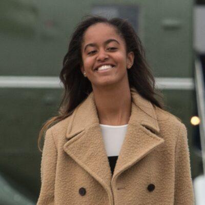 Malia Obama smiling in a beige overcoat