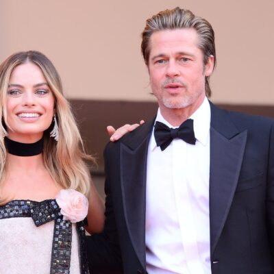 Margo Robbie, and a beaded dress, stands with Brad Pitt, in a black tux, on the red carpet