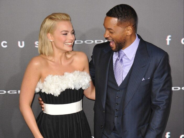 Margot Robbie and Will Smith laugh together on the red carpet for the premiere of their film Focus