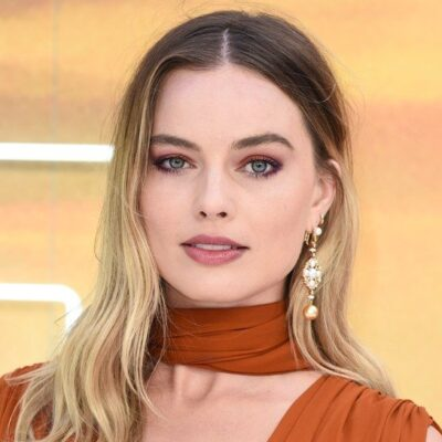 Margot Robbie is a very low cut rust-colored dress.