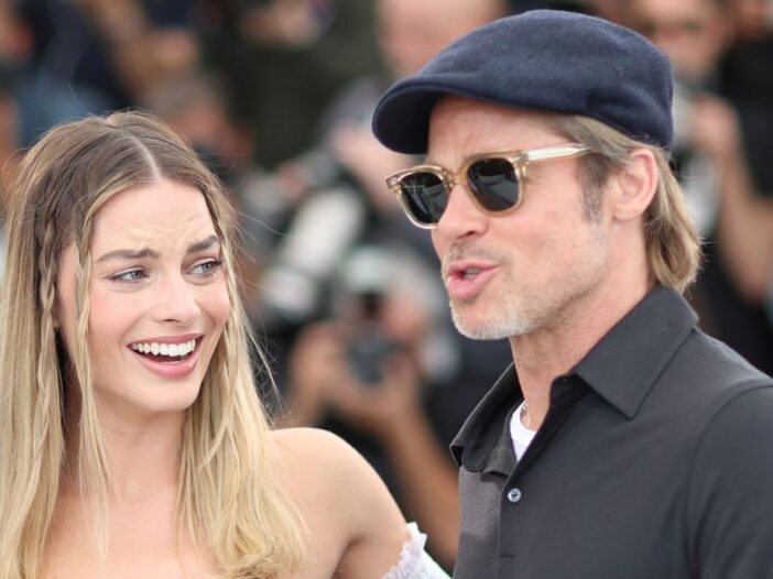 Margot Robbie wearing a strapless dress standing with Brad Pitt, who's wearing a polo shirt and sung