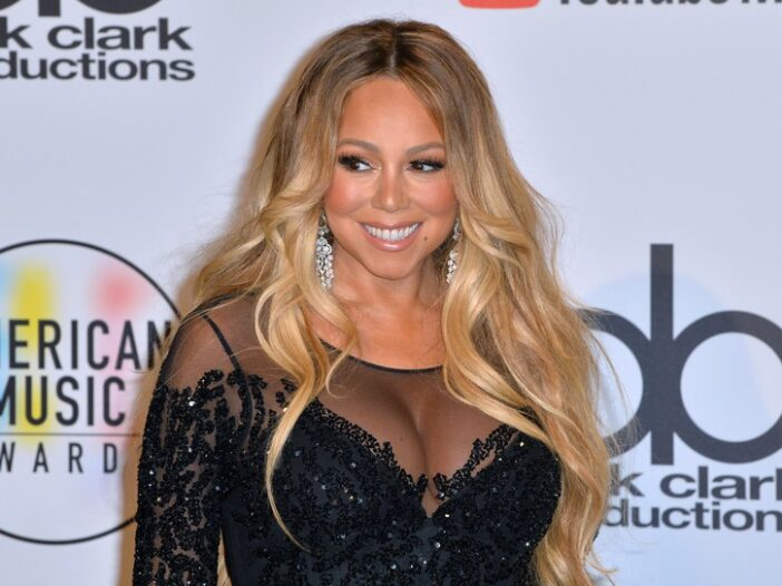 Mariah Carey smiling at a red carpet event in a black sequin dress.