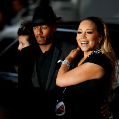 Marian Carey and Nick Cannon, both dressed in all black, arrive at a movie premiere