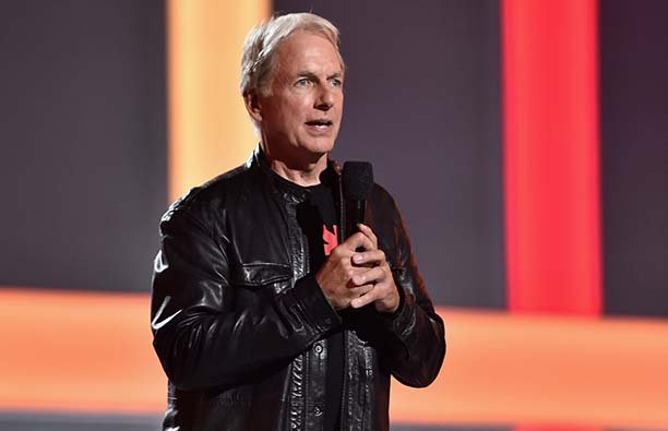 Mark Harmon in a leather jacket speaking into a microphone