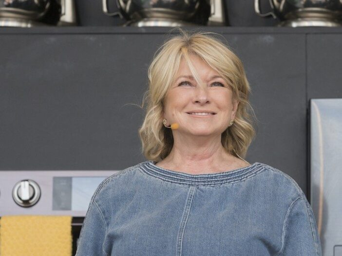 Martha Stewart smiling and speaking in a blue denim shirt against a gray background