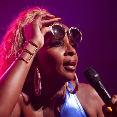 Mary J Blige wearing a blue top and performing onstage