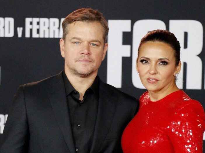 Matt Damon in a black suit posing with wife Luciana Barroso in a red dress