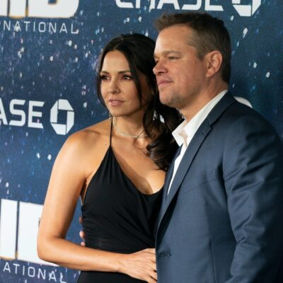 Matt Damon in a grey suit with his arm around wife Luciana Barroso in a black dress