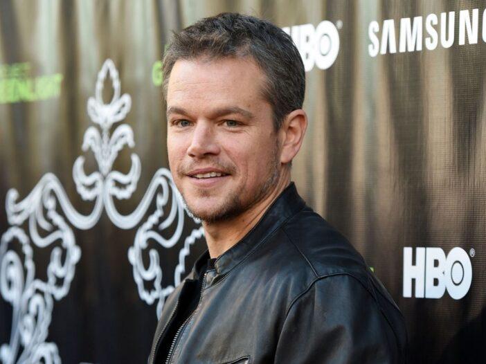 Matt Damon wearing a black leather jacket on the red carpet.