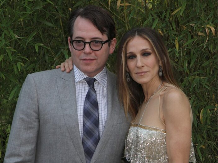 Matthew Broderick wearing a gray suit posing with Sarah Jessica Parker, wearing a gold dress
