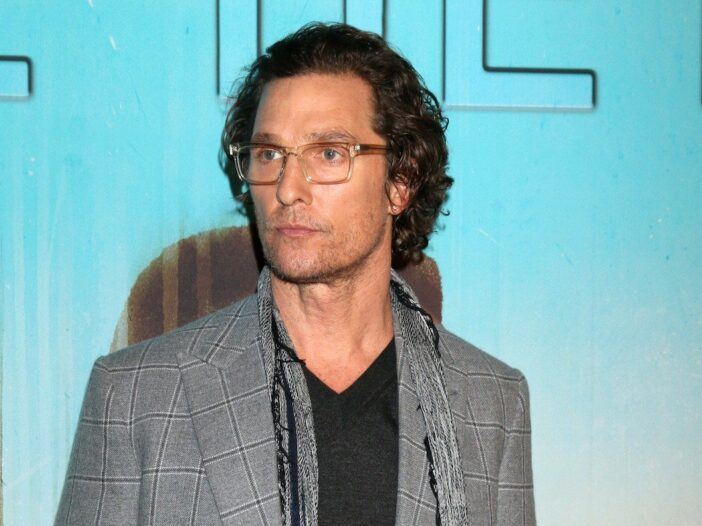 Matthew McConaughey looking off in a grey suit with glasses