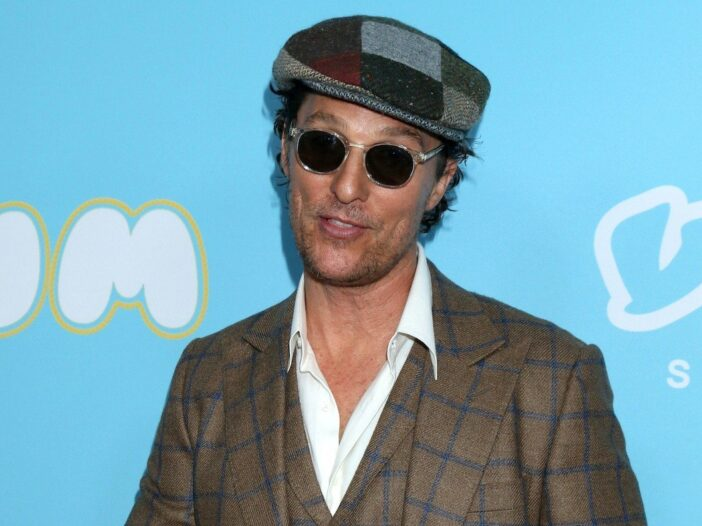 Matthew McConaughey smiling in a brown striped suit with a hat and sunglasses