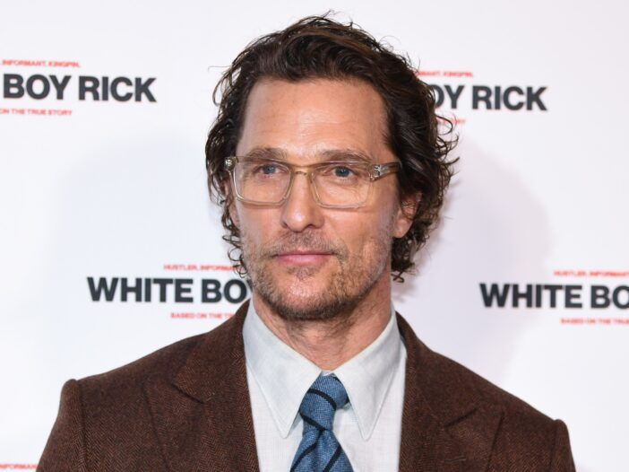 Matthew McConaughey wearing a tan jacket and blue tie and eyeglasses.