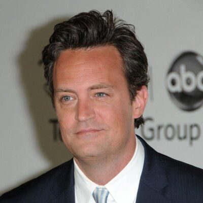 Matthew Perry wearing a dark suit with a blue stripped tie on the red carpet