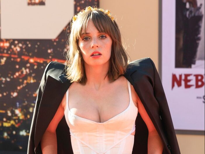 Maya Hawke wearing a low cut bustier and blazer over her shoulders on the red carpet