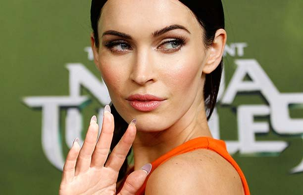 Megan Fox holdling up her hand and waving