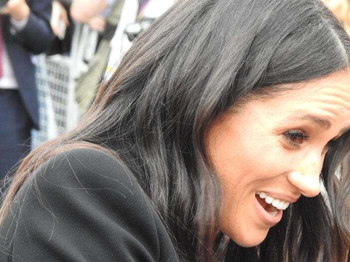 Meghan Markle, in a black coat, smiles at onlookers as she greets a crowd of supporters