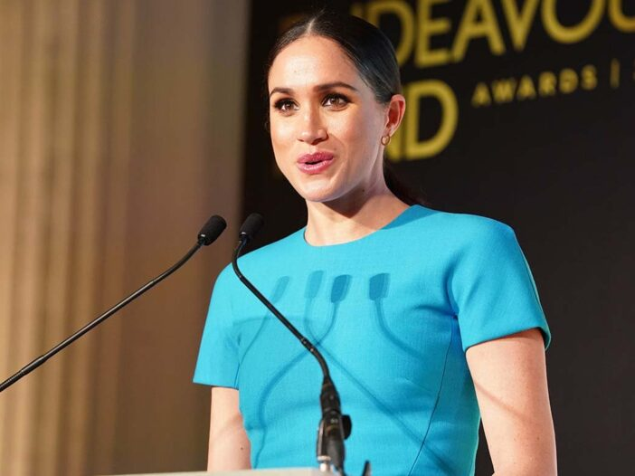 Meghan Markle in a blue dress standing at a podium