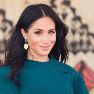 Meghan Markle in a green dress, smiling with her hair blowing slightly in the wind.