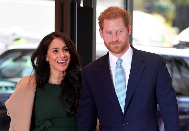 Meghan Markle in a light tan coat over a green dress smiles and holds hands with Prince Harry in a n