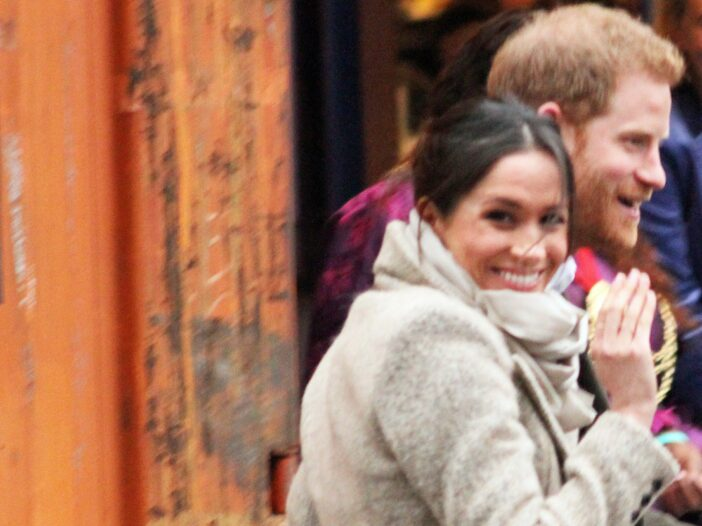 Meghan Markle in a white coat, waving with Prince Harry in a suit.