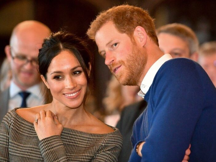 Meghan Markle on the left, leaning in to talk to Prince Harry, on the right. Both smiling.