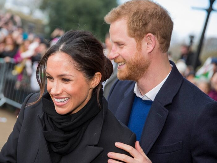 Meghan Markle on the left, standing in front of Prince Harry who has his hand on her shoulder.