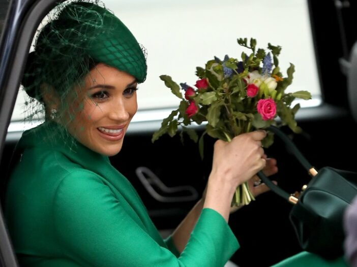 Meghan Markle riding in a car in a green dress with a bouquet of flowers in her hand