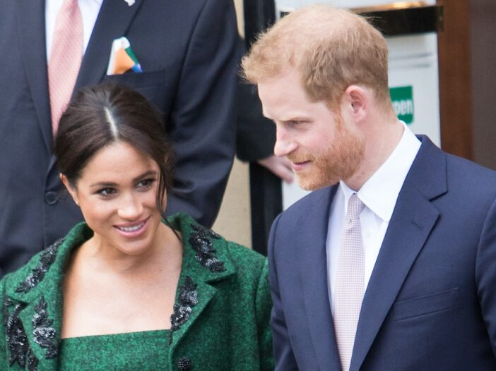 Meghan Markle smiling in a green dress and jacket with Prince Harry in a navy suit