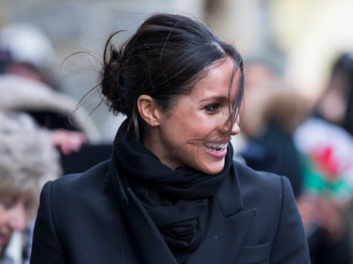 Meghan Markle smiling outside dressed in a black jacket and scarf