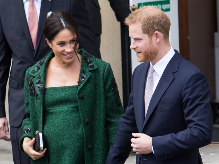 Meghan Markle wearing a green dress and coat walking with her husband Prince Harry, in a navy suit