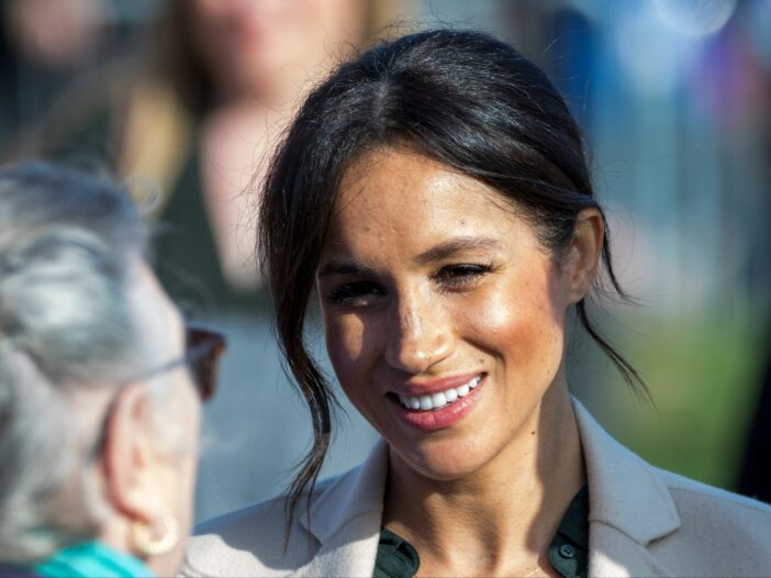 Meghan Markle wears a beige coat over a green shirt while greeting people