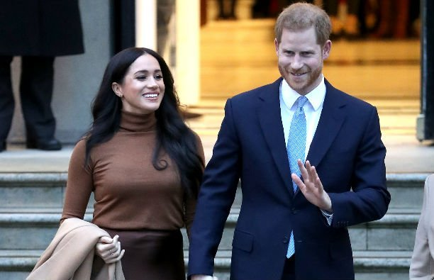 Meghan Markle wears a bron turtleneck and a brown skirt, Prince Harry wears a navy suit and a bright