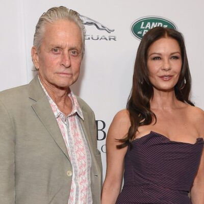 Michael Douglas in a tan jacket holding hands with wife Catherine Zeta-Jones in a black and red dress