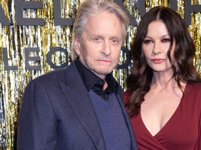 Michael Douglas wearing a dark blazer and sweater stands with Catherine Zeta-Jones, in a red dress