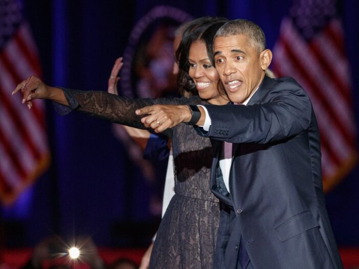 Michelle and Barack Obama pointing at something off-camera, together on stage at a campaign event.