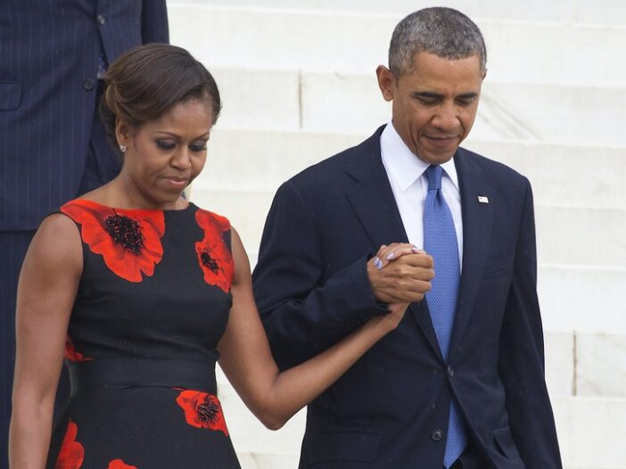 Michelle Obama in a black dress walking down stairs with husband Barack Obama in a black suit