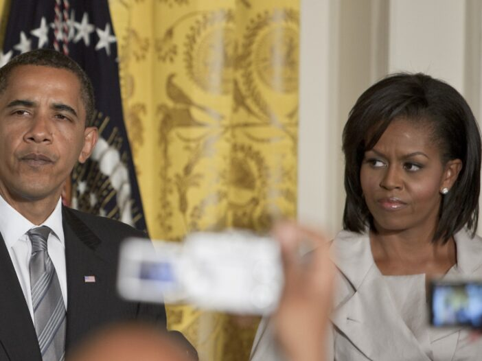 Michelle Obama on the right, looking suspiciously at Barack Obama on the left.