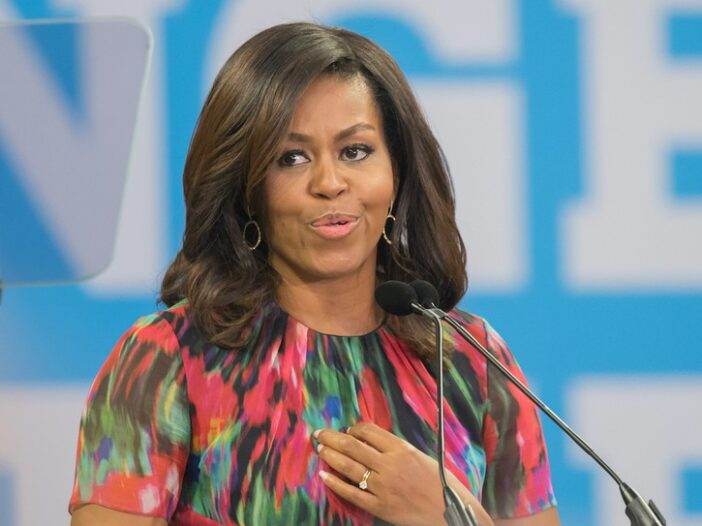 Michelle Obama speaking at a podium in a green, red, and blue top against a blue background