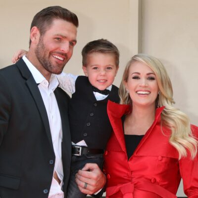 Mike Fisher in a black suit with Carrie Underwood in a red trench coat with son Isaiah at a red carpet event.